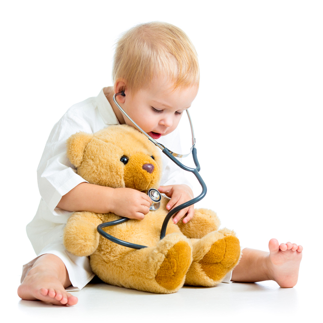 Baby giving teddy bear a checkup