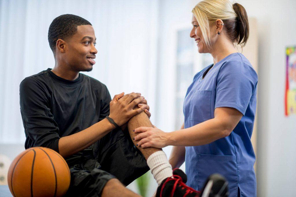 Doctor checking an athlete's injured knee