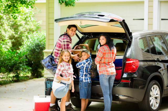 family packing a car for vacation