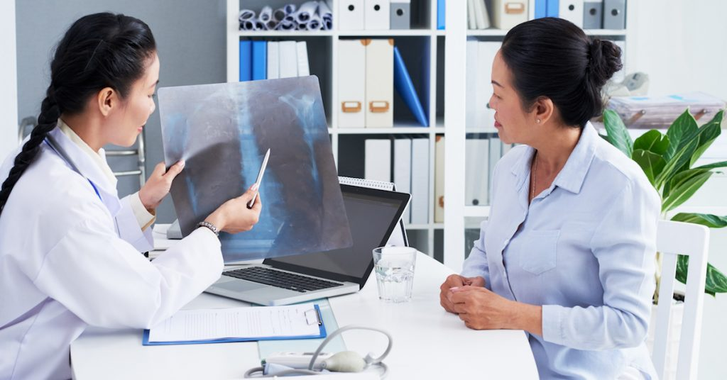 Doctor showing chest x-ray to patient