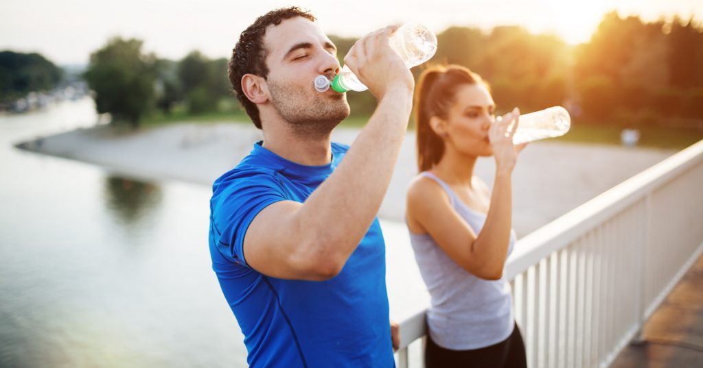 Picture of a couple staying hydrated after workout.