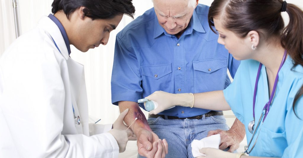Picture of a doctor and nurse looking at a burn wound.