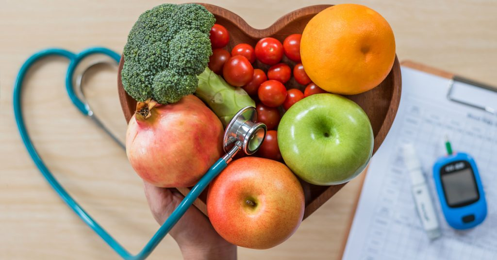 Picture of healthy food and a diabetic measuring tool kit on a table.