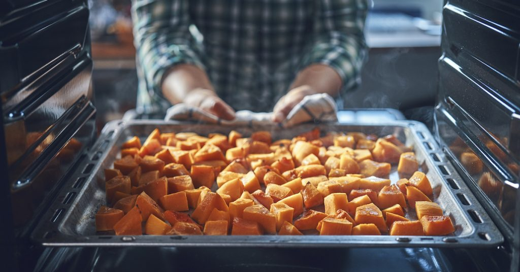 Picture of someone pulling pumpkin pieces out of the oven.