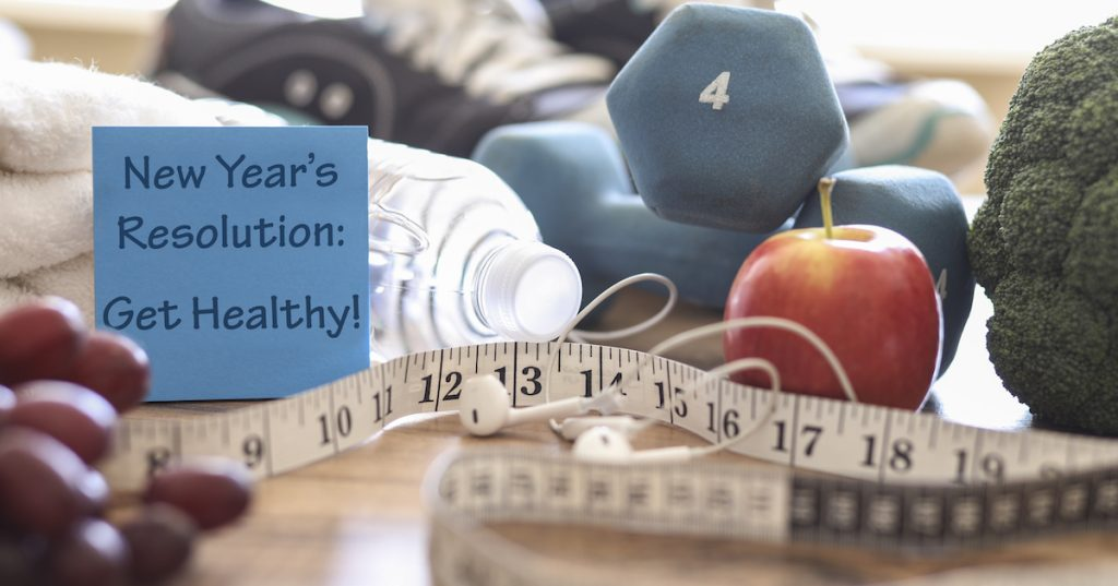 Picture of weights, healthy food, and a measuring tape on a table.