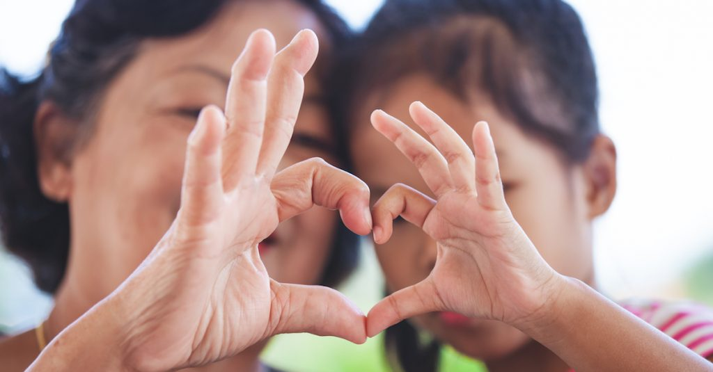 Picture of two people making a heart with their hands.