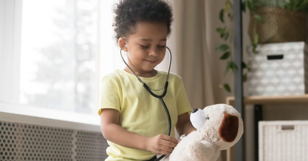 Image of little boy checking his teddy bear's heart