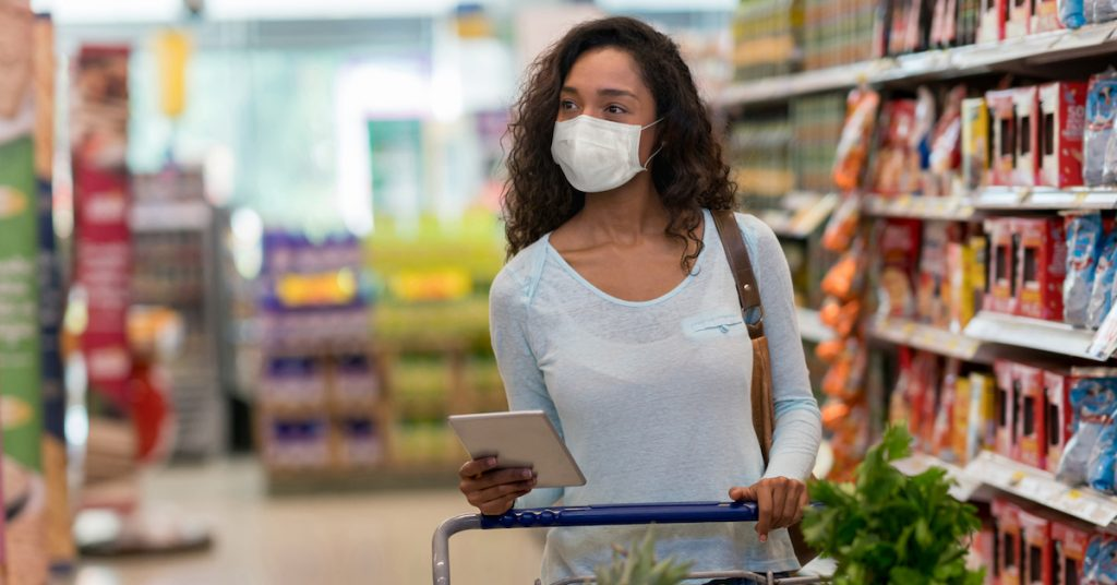 Picture of woman shopping at the supermarket wearing a facemask