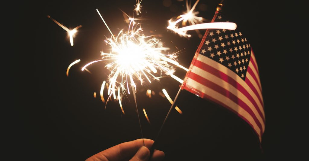 picture of Hand holding lit sparkler with American Flag