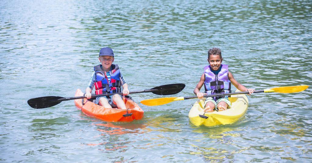 Two Kids in kayaks on a lake